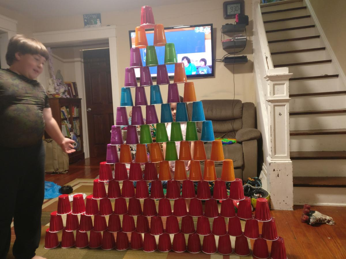 boy standing next to tower made of plastic cups.