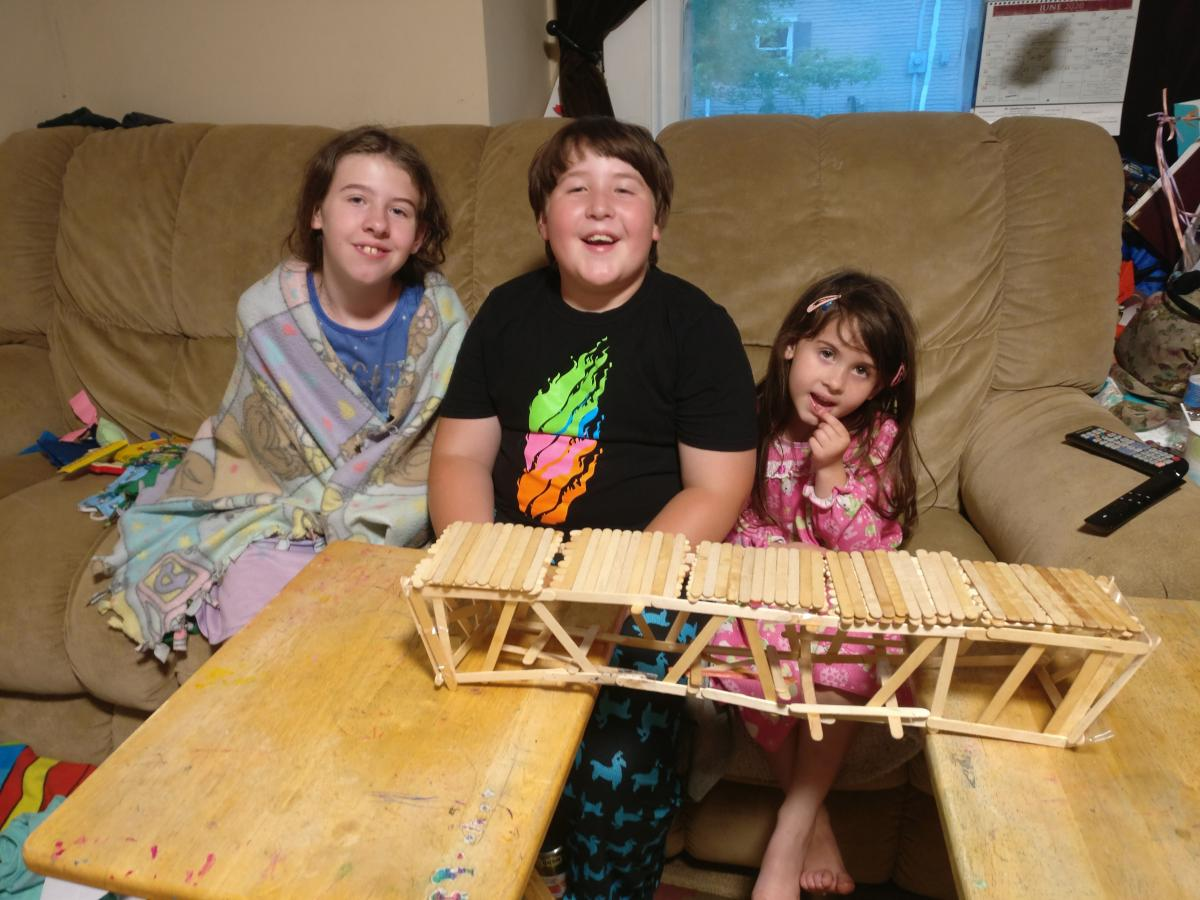 three children sitting in front of a popsicle stick bridge
