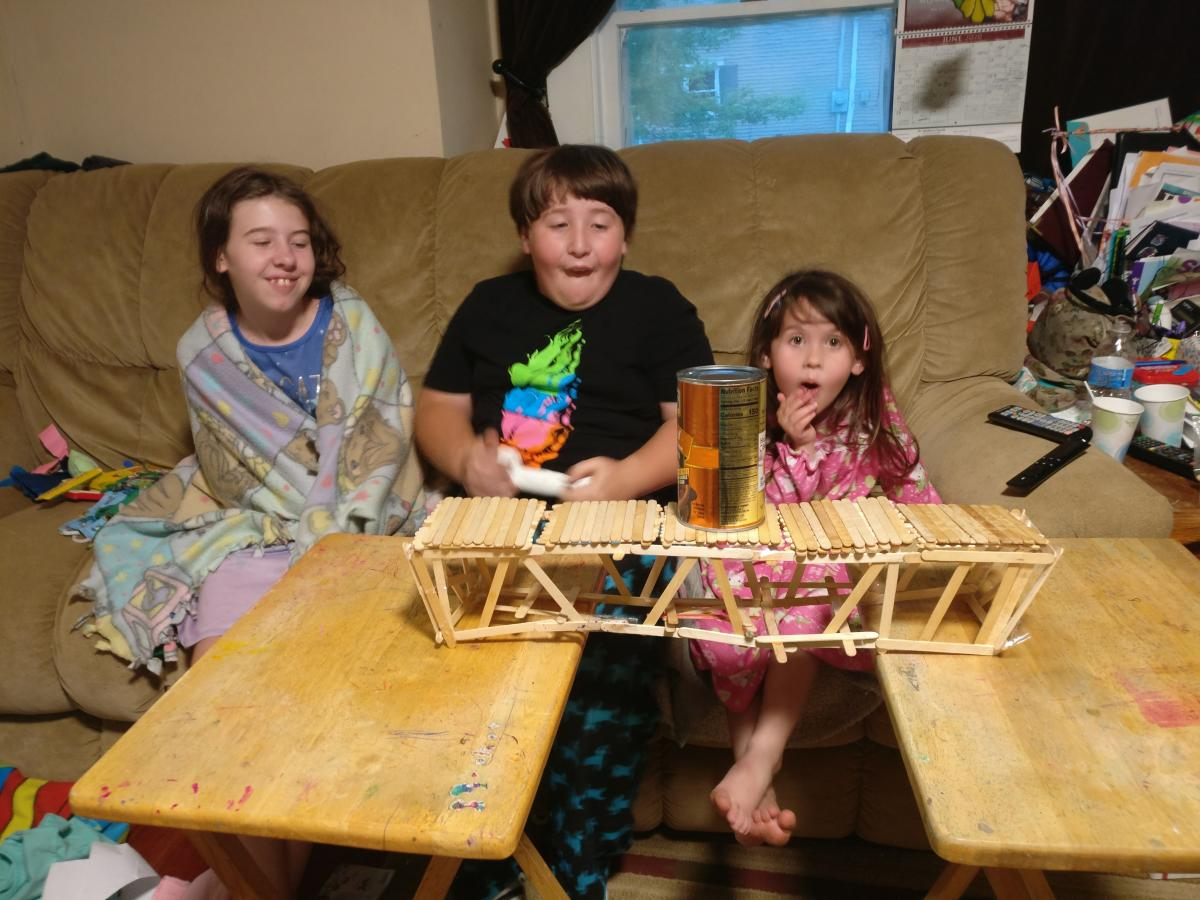 three children sit in front of their popsicle bridge testing its strength with a heavy can of food.