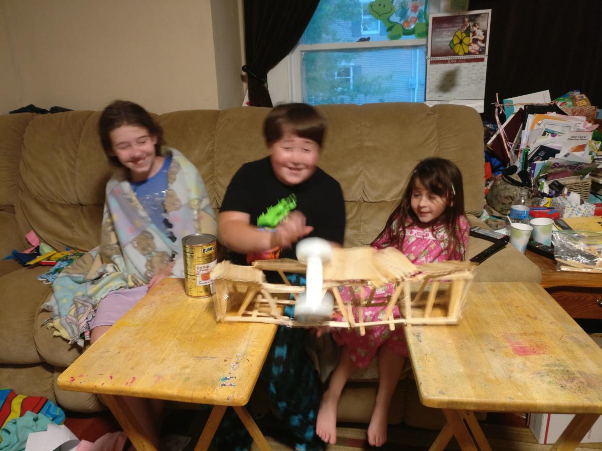 Three children laugh as their popsicle bridge collapses.