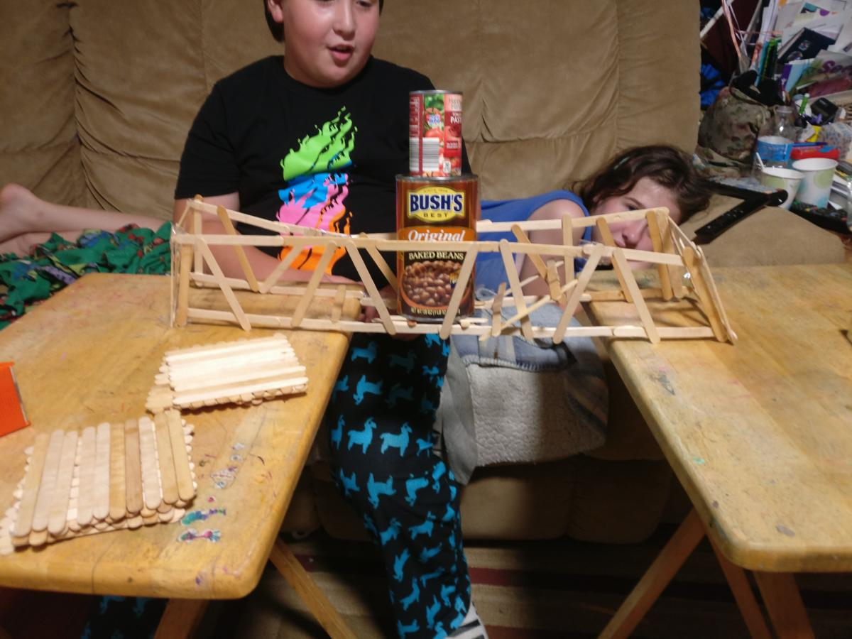 Boy looks at popsicle bridge as it is stressed under the weight of two cans of food.
